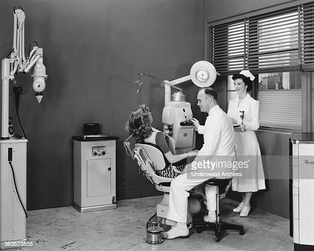 A woman in a dentists's chair with the dentist and his assistant ready to go to work circa 1958