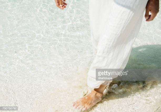 A woman in a dress is walking along the seashore