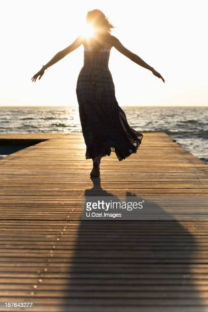 a woman in a dress on a dock with her arms spread - woman leg spread stock photos and pictures