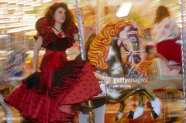 A woman in a elaborate ruffled dress rides a carousel during Abril Feria celebrations in Seville Spain