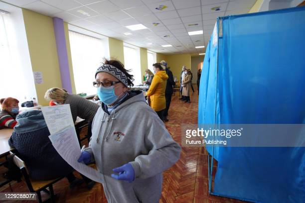 Woman in a face mask and latex gloves visits a polling station to cast her vote in the 2020 Ukrainian local elections, Kharkiv, northeastern Ukraine....