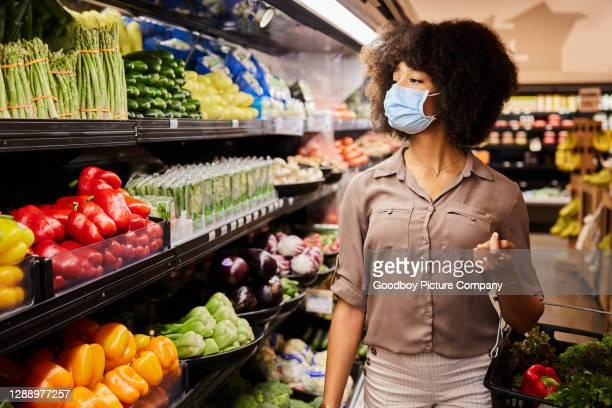 frau in einer gesichtsmaske, die produkte in regalen in einem supermarkt betrachtet - auslage stock-fotos und bilder