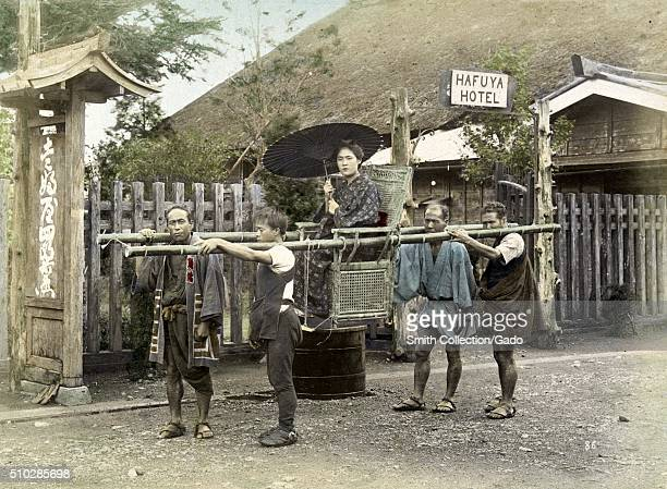 A woman in a fine kimono holding an umbrella is being transported in a kago that consists of a chair suspended from two long sections of bamboo four...