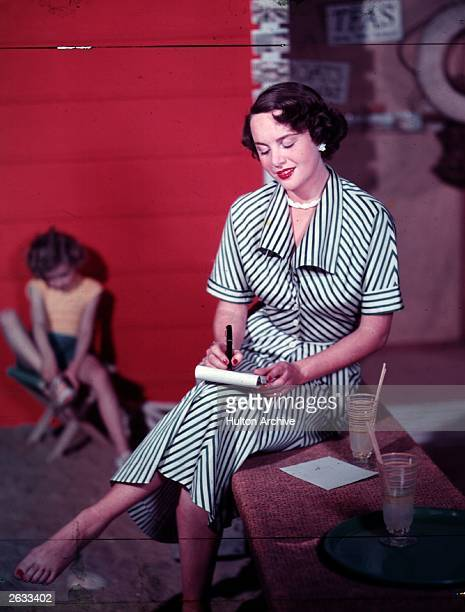 A woman in a green striped day dress writing a letter in holiday surroundings