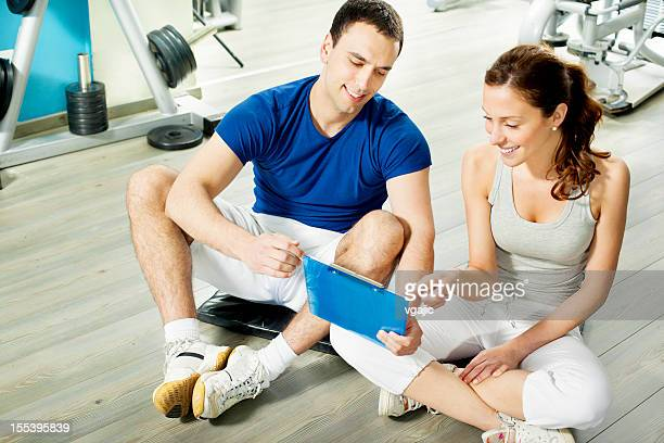 Woman in a gym with personal trainer.