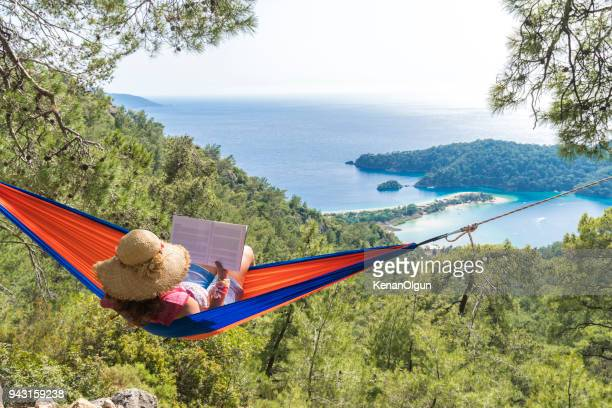 woman in a hammock with book on holiday - aegean turkey stock pictures, royalty-free photos & images