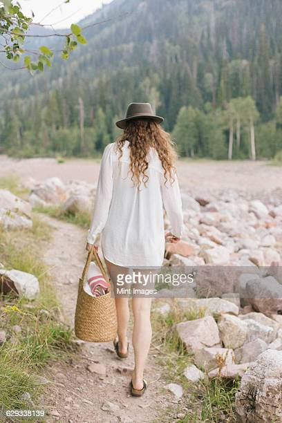 a woman in a hat and white shirt with a basket, by the shore of a mountain lake.  - wit hemd stockfoto's en -beelden