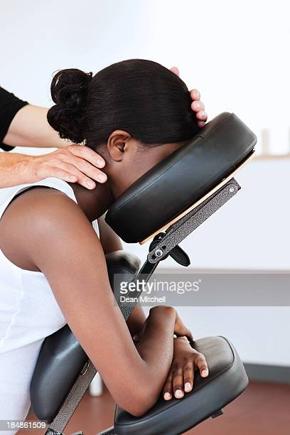 woman in a head massage chair - black massage therapist stock photos and pictures