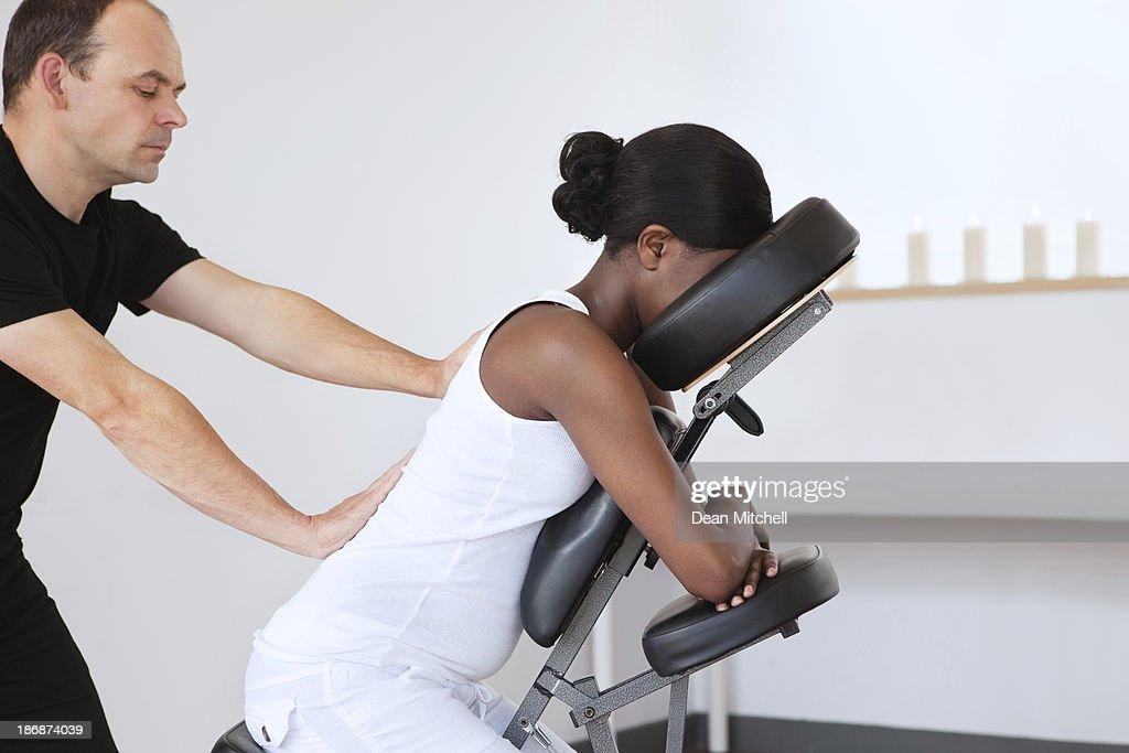 Mulher em uma cadeira de massagem de cabeça : Foto de stock