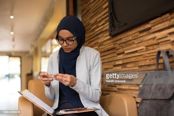woman in a hijab working - zurückhaltende kleidung stock-fotos und bilder