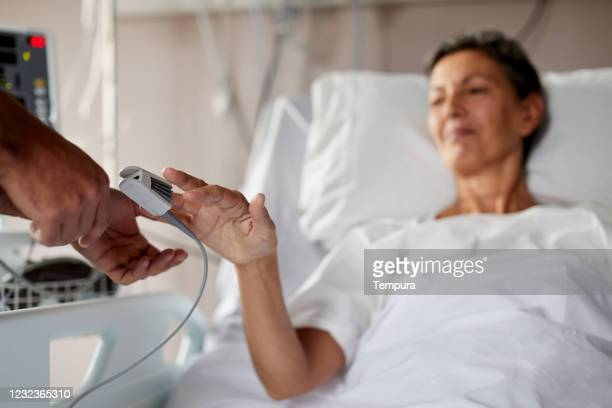 woman in a hospital bed with a finger oximeter - pulse oximeter stock pictures, royalty-free photos & images