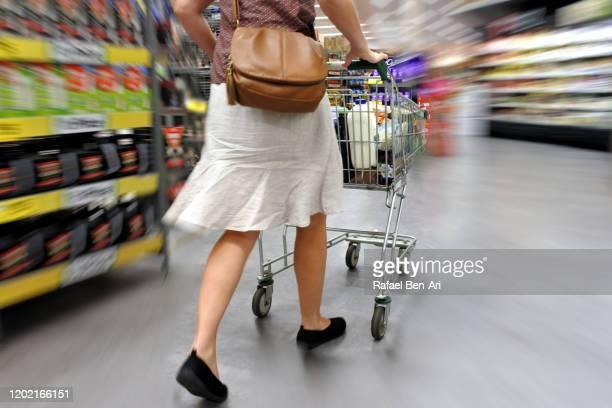 woman in a hurry rushing through supermarket fast during grocery shopping - rafael ben ari 個照片及圖片檔
