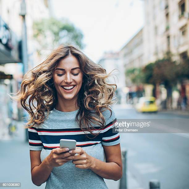 Woman in a hurry texting on the street