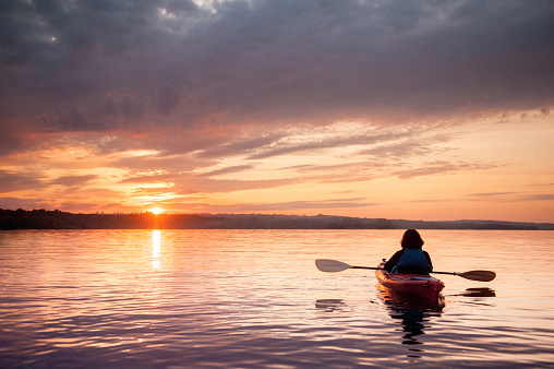 Woman in a kayak on the river on the scenic sunset 1059748342