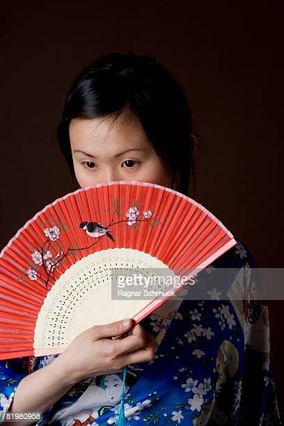 A woman in a kimono holding a folding fan