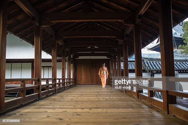 Woman in a kimono walking through a temple corridor