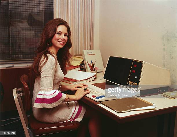 A woman in a knit dress with flared sleeves works at an early model desktop computer made by Servus 1970s