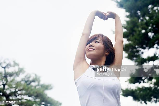a woman in a kyoto park, wearing headphones. wearing jogging kit and stretching before exercise. - sleeveless stock pictures, royalty-free photos & images