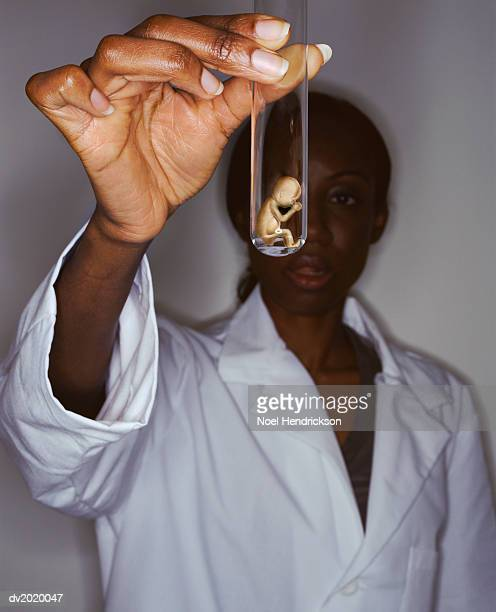Woman in a Lab Coat Holds Out a Fetus Inside a Test Tube