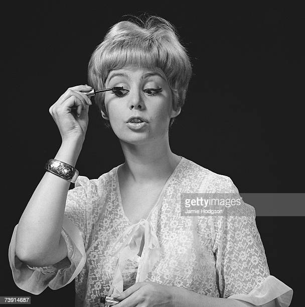 A woman in a lacy peignoir applies her mascara circa 1970