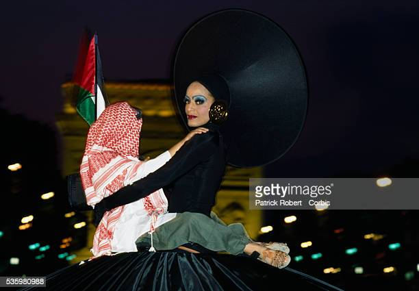 A woman in a large hat carrying a child parades past the Arc de Triomphe during the 200th anniversary of Bastille Day The event attended by hundreds...