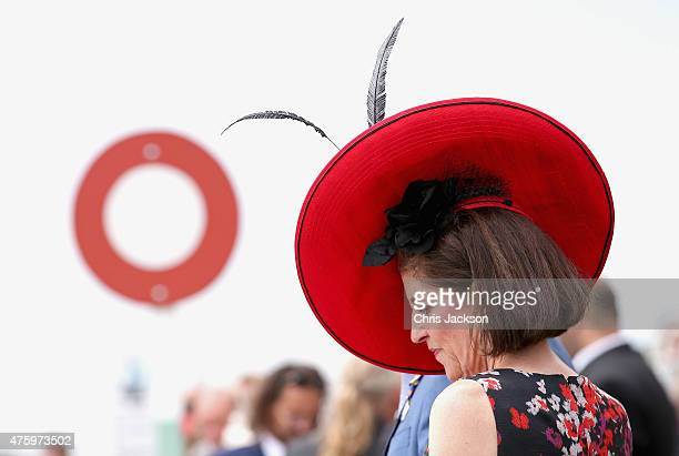A woman in a large red hat checks her race card at the finish line during Ladies Day at the Investec Derby Festival on June 5 2015 in Epsom England