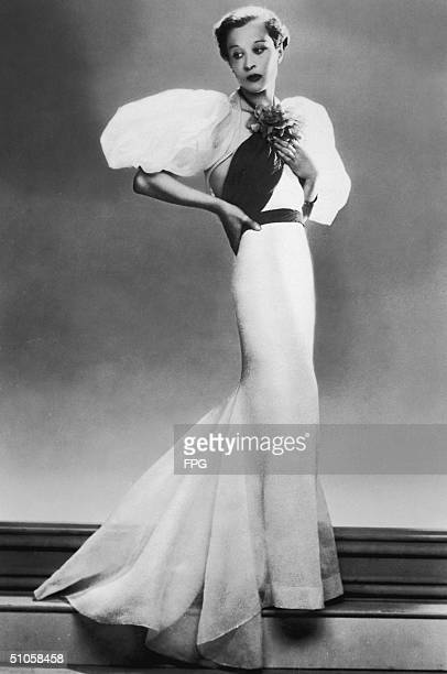 A woman in a long evening gown with puffball sleeves circa 1930