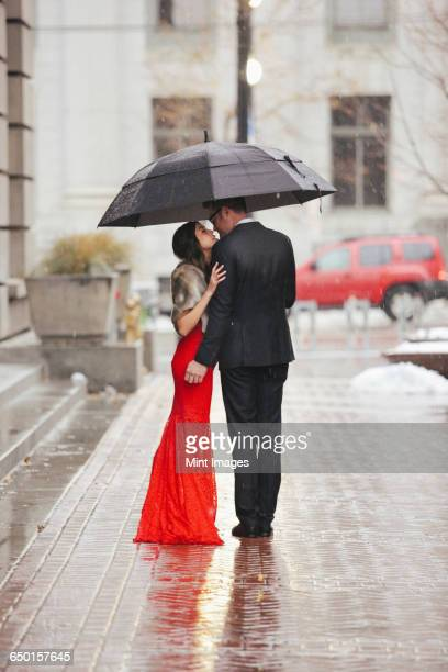 A woman in a long red evening dress with fishtail skirt and a fur stole, and a man in a suit kissing under an umbrella on a street.