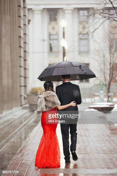 a woman in a long red evening dress with fishtail skirt and a fur stole, and a man in a suit, walking through a city. - evening wear stock pictures, royalty-free photos & images