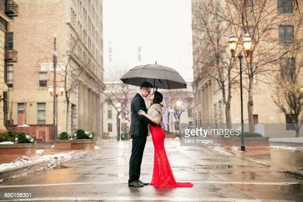 A woman in a long red evening dress with fishtail skirt and a fur stole, and a man in a suit, kissing under an umbrella in the city.