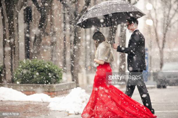 a woman in a long red evening dress with fishtail skirt wearing a fur stole, and a man in a suit, walking through snow in the city.  - utah wedding stock pictures, royalty-free photos & images