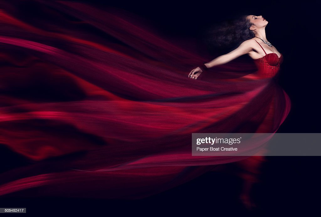 Woman in a long red flowing dress : Stock Photo
