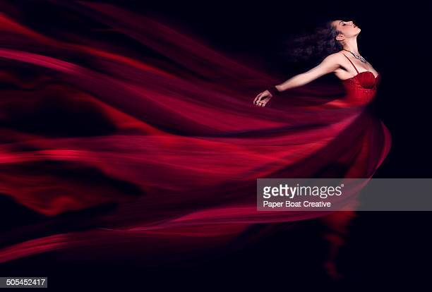 woman in a long red flowing dress - satin dress stock photos and pictures