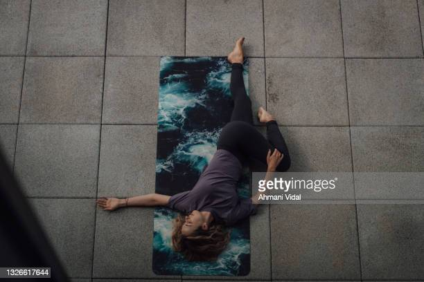 woman in a low yoga pose - one mid adult woman only stock pictures, royalty-free photos & images