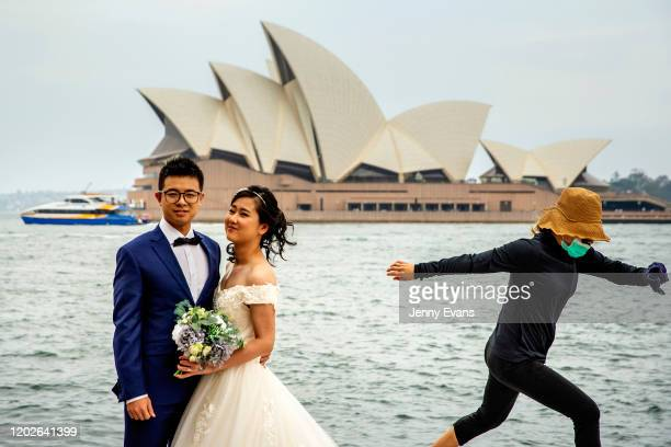 A woman in a mask jumps out of the way of a wedding photo at The Rocks on January 29 2020 in Sydney Australia The coronavirus which originated in...