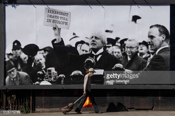 A woman in a mask walks past a satirical poster from the group Led By Donkeys depicting Boris Johnson as former British prime minister Neville...