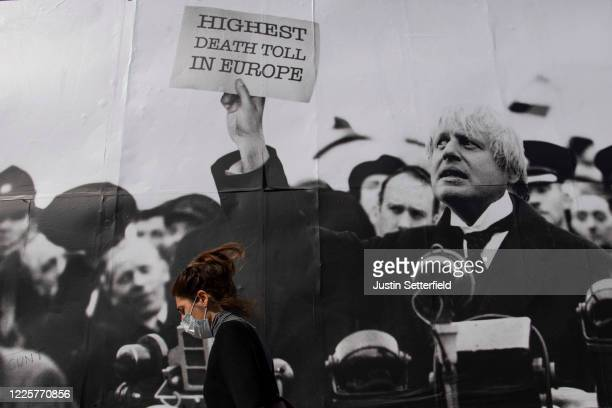 Woman in a mask walks past a satirical poster from the group Led By Donkeys depicting Boris Johnson as former British prime minister Neville...