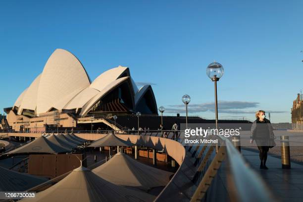 Woman in a mask walks through the Sydney Opera House forecourt on August 17, 2020 in Sydney, Australia. New South Wales remains on high alert as new...
