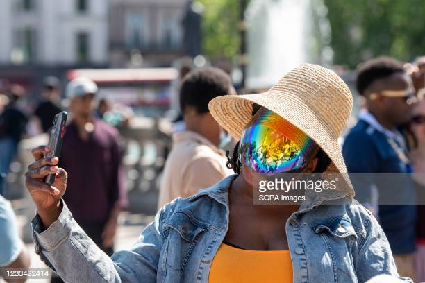 Woman in a mirrored face covering seen takes a selfie in Trafalgar Square during the demonstration. A protest in solidarity with the Democracy Day...