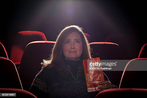 Woman in a movie theater watching a sad movie