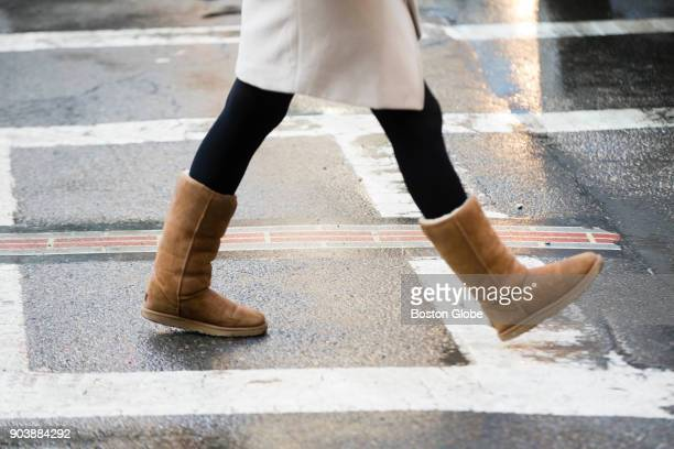 A woman in a pair of UGG boots makes her way along Washington Street in Boston on Jan 9 2018 The boots are still popular amid the ice and slush on...