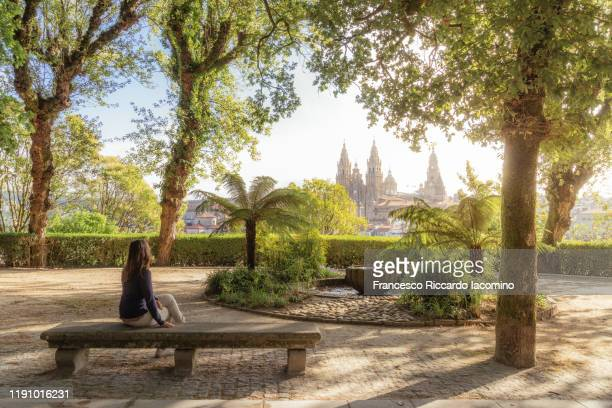 woman in a park bench watching santiago de compostela cathedral at sunrise, park and sunny sky. galicia, spain - cattedrale di san giacomo a santiago di compostela foto e immagini stock