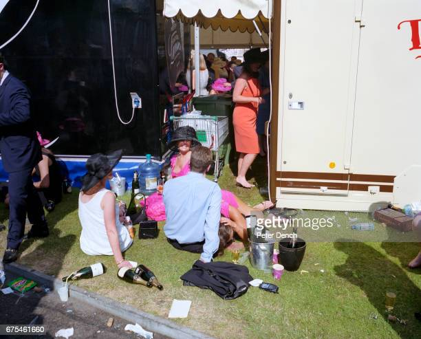 A woman in a pink dress lies down on the grass to be sick during Ladies Day at Royal Ascot she was later attended to by the onsite medical team and...