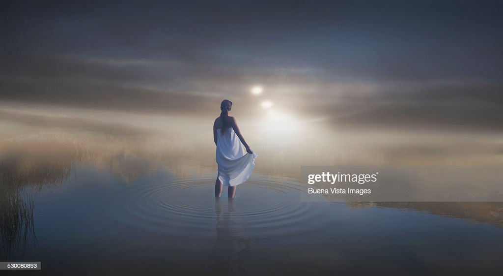 Woman in a pond in the mist : Stock Photo