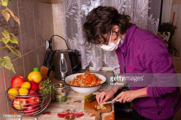 A woman in a protective sanitary mask prepars traditional Polish salad as a treat for Easter holiday during Coronavirus pandemic while forced to stay...