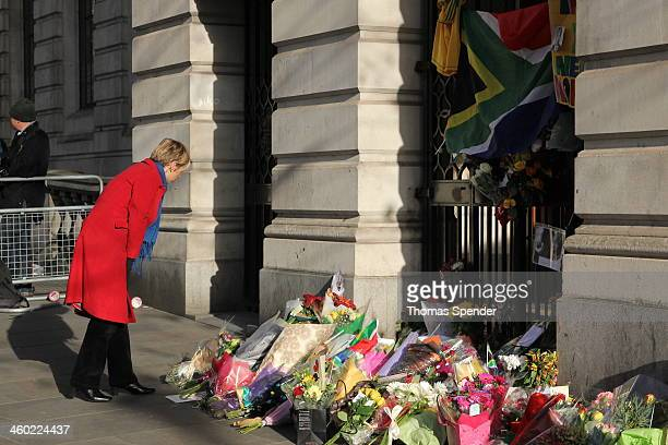 Woman in a red coat leaves flowers outside South Africa House in London as a tribute to Nelson Mandela after his death.
