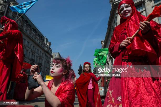 A woman in a red costume applies makeup during a protest against climate change in the middle of Oxford Circus on 15th April 2019 in London United...