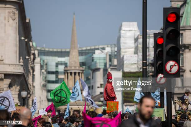 A woman in a red costume stands on a stage surrounded by flags depicting the logo of Extinction Rebellion during a protest against climate change in...