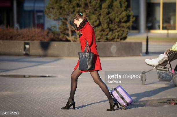 A woman in a red dress carrying a small suitcase is seen in Warsaw Poland on April 2 2018