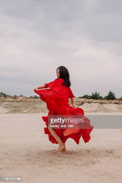 woman in a red dress dancing in the desert, russia - red dress stock pictures, royalty-free photos & images